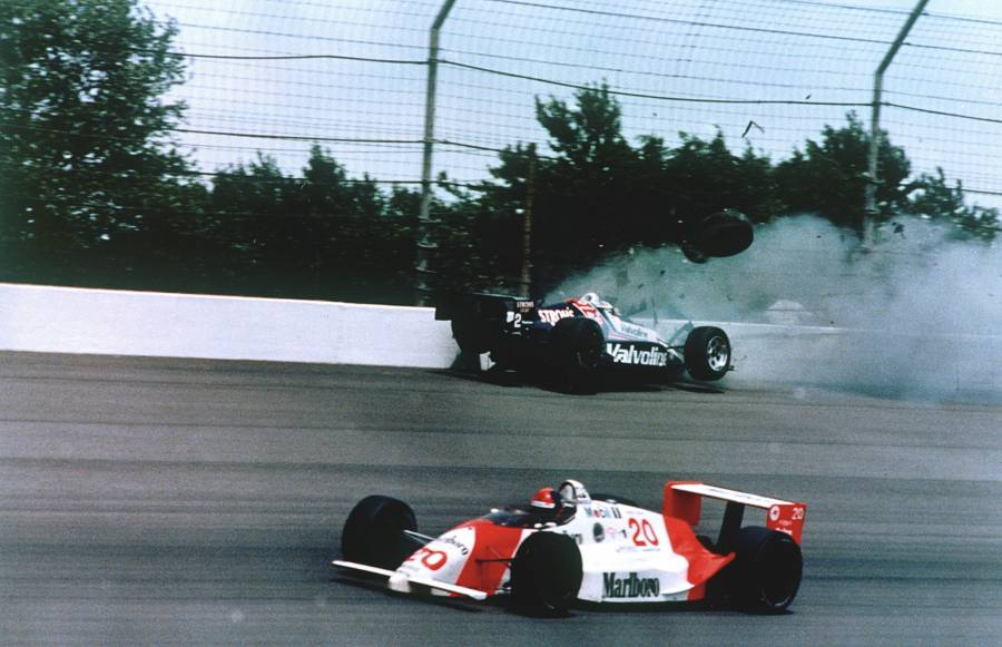 FILE - In this May 28, 1989, file photo, Emerson Fittipaldi, bottom, takes the lead with less than two laps remaining as Al Unser Jr. crashes into the wall during the 73rd running of the Indianapolis 500 auto race at Indianapolis Motor Speedway.