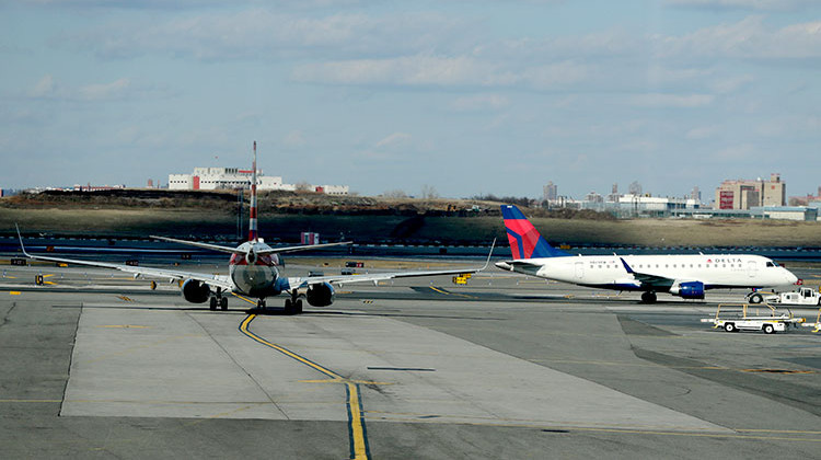 "An American Airlines jet, left, waits for a Delta Airlines jet to pass by before following it onto the runway at LaGuardia Airport, Friday, Jan. 25, 2019, in New York. The Federal Aviation Administration reported delays in air travel Friday because of a ""slight increase in sick leave"" at two East Coast air traffic control facilities. - AP Photo/Julio Cortez"