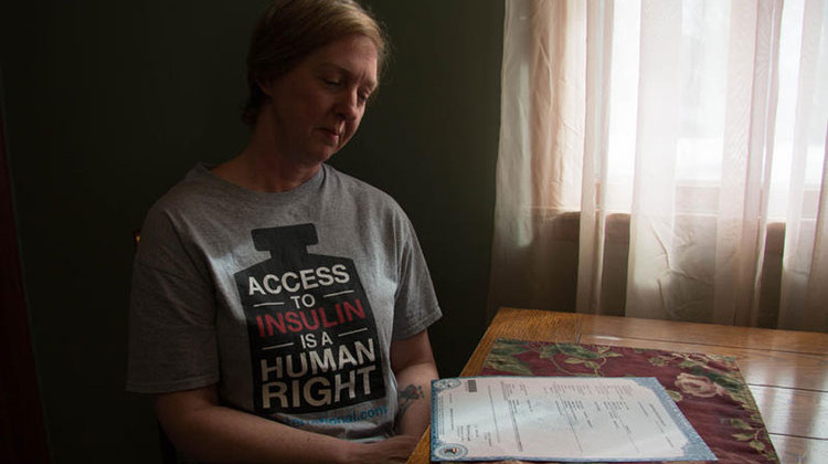 Nicole Smith-Holt looks at her son Alec's death certificate in her Richfield, Minn. home. Alec died in 2017 from diabetic ketoacidosis. - Bram Sable-Smith/KBIA/Side Effects Public Media