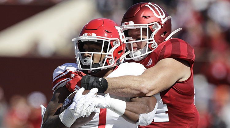 FILE - In this Oct. 12, 2019, file photo, Rutgers running back Isaih Pacheco, left, is tackled by Indiana linebacker Thomas Allen, right, during the first half of an NCAA college football game, in Bloomington, Ind. Allen had season-ending surgery on his left shoulder in November. His recovery plan changed dramatically when the coronavirus pandemic led to the suspension of athletic activities. - AP Photo/Darron Cummings, File