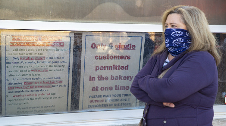 A masked customer waits in line next to a sign outlining the rules to enter at the Long's Bakery Shop in Indianapolis, Friday, May 1, 2020. The bakery reopened after closing it doors due to COVID-19. The bakery, considered an essential business, reopened as Indianapolis extended the city's stay-at-home order to May 15. Customers waited in the hour-long line to purchase the shop's signature yeast glazed donuts. - AP Photo/Michael Conroy