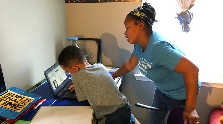 Tiffany Shelton helps her 7-year-old son, P.J. Shelton, a second-grader, during an online class at their home in Norristown, Pa., on Thursday, Sept. 3, 2020. Norristown Area School District plans to offer online-only instruction through at least January 2021. - AP Photo/Michael Rubinkam