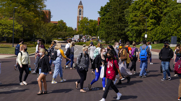 Masked students cross an intersection on the campus of Ball State University in Muncie, Ind., Thursday, Sept. 10, 2020. College towns across the U.S. have emerged as coronavirus hot spots in recent weeks as schools struggle to contain the virus. - AP Photo/Michael Conroy
