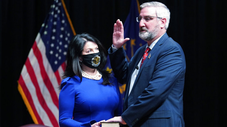 Eric Holcomb is sworn in as Governor of Indiana by Chief Justice Loretta H. Rush in a Bible his wife Janet held during an opening ceremony at the Indiana State Museum in Indianapolis on Monday, January 11, 2021.  - AP Photo / Darron Cummings