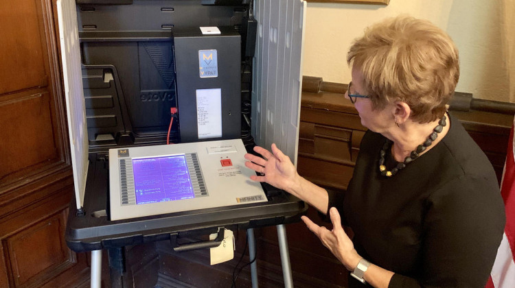 Secretary of State Connie Lawson demonstrates the use of a paper audit trail on an electronic voting machine. - Brandon Smith/IPB News