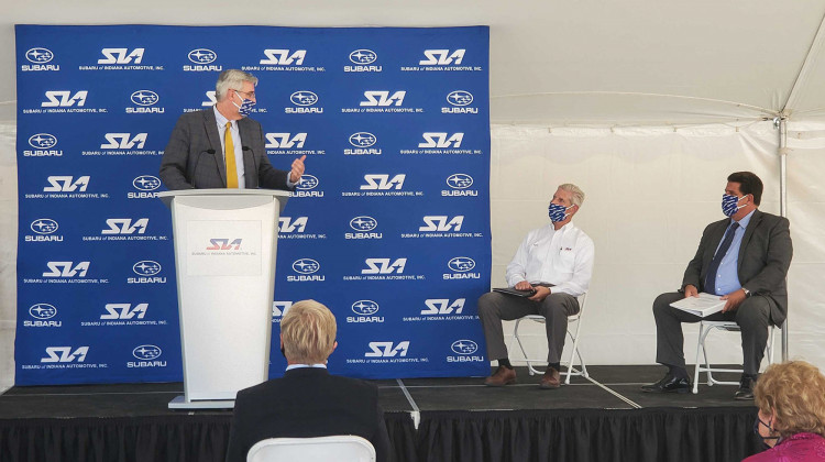 (Left to right) Gov. Eric Holcomb speaks at Subaru of Indiana Automotive ground breaking with SIA Vice President Scott Brand and Lafayette Mayor Tony Roswarski sitting on stage. - Samantha Horton/IPB News