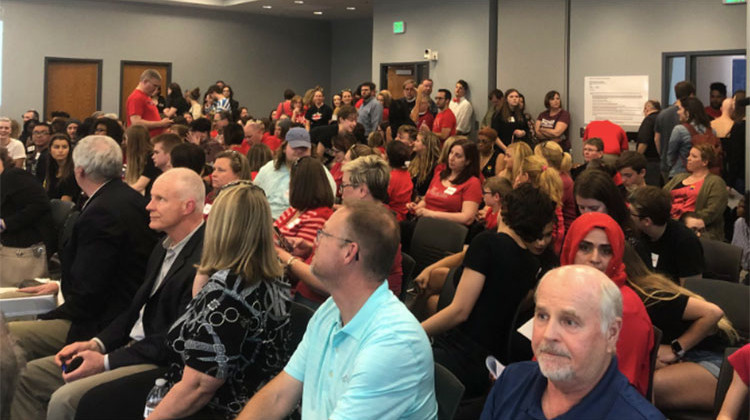 Hundreds of people in red t-shirts filled the board room, a hallway, and overflow room at the HSE central services building Wednesday night. - Carter Barrett/WFYI