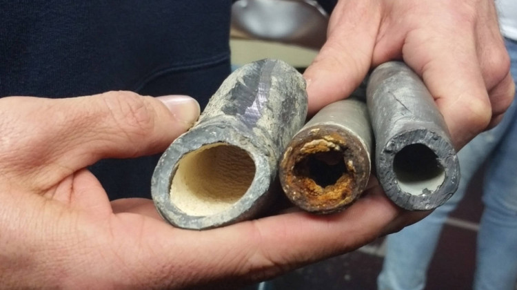 An EPA civil engineer shows how corrosion control treatments can affect lead pipes. The one on the left was treated, the middle one was not, and the one on the right is a new pipe - Lauren Chapman/IPB News