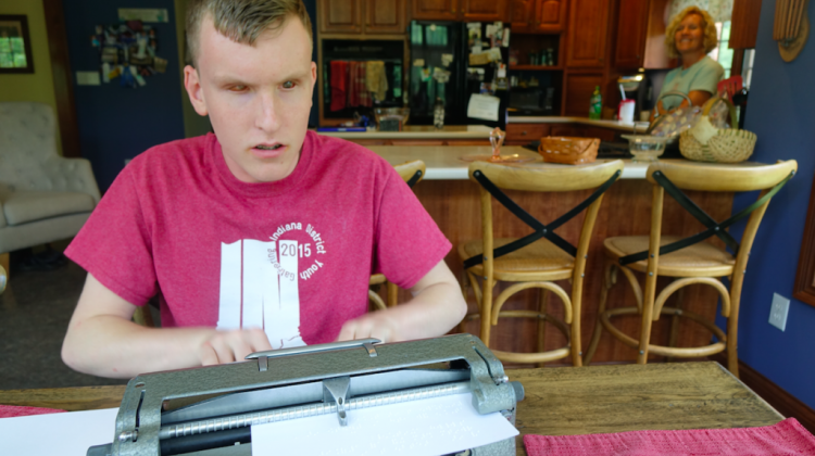 Mitchell Bridwell types on a Perkins Unimanual Brailler in the kitchen of his Pittsboro home as his mother Marta stands in the back, on Wednesday, June 14, 2017. Bridwell, 16, is one of 10 students from the U.S. and Canada to compete in the national Braille Challenge for his age group in Los Angeles on June 17, 2017. - Eric Weddle/WFYI Public Media