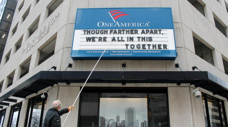 A man adjusts the One America sign in downtown Indianapolis. It usually displays a pun, but the message shortly before the governor's address reads: 'Although farther apart, we're all in this together.' - Lauren Chapman/IPB News