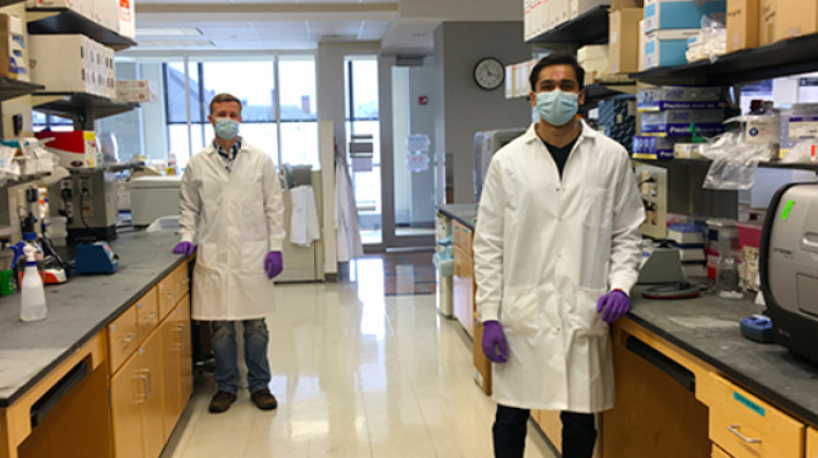 Laboratory technicians Justin Lange, left, and Akanksh Shetty observe social distancing while creating viral transport media at the University of Illinois. The fluid is used to preserve patient test samples for COVID-19. - Courtesy of Ann Hyoung Sook/University of Illinois
