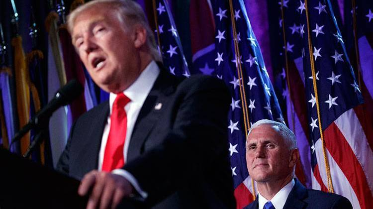 Vice president-elect Mike Pence, right, watches as President-elect Donald Trump speaks during an election night rally, Wednesday, Nov. 9, 2016, in New York. - AP Photo/ Evan Vucci