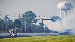 Indianapolis 500 Champion Alexander Rossi drives down the backstretch of the Indianapolis Motor Speedway as two-time Red Bull Air Race world champion KirbyChambliss flies above. - Courtesy Red Bull Media House
